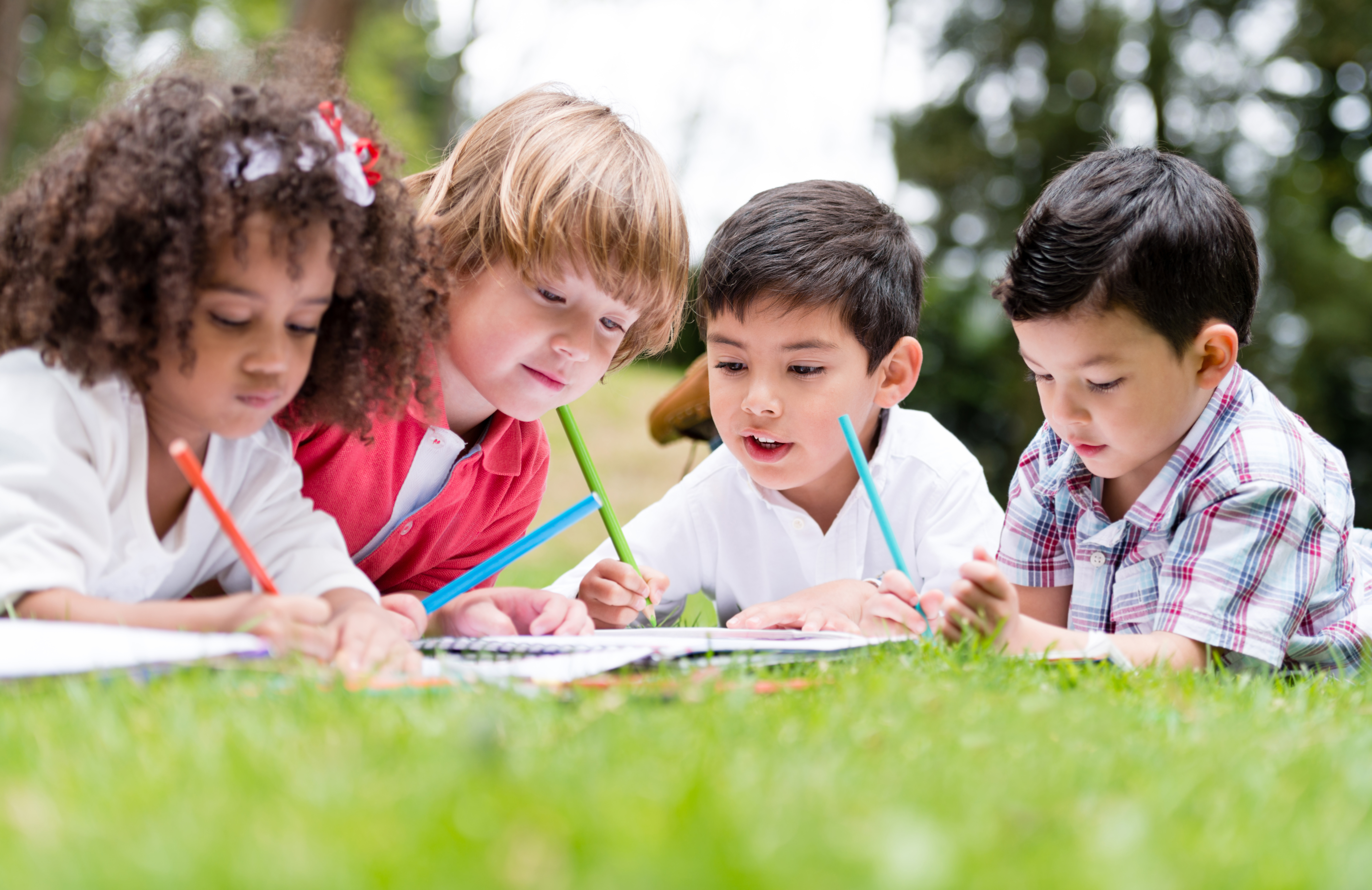 children coloring laying in the grass outside